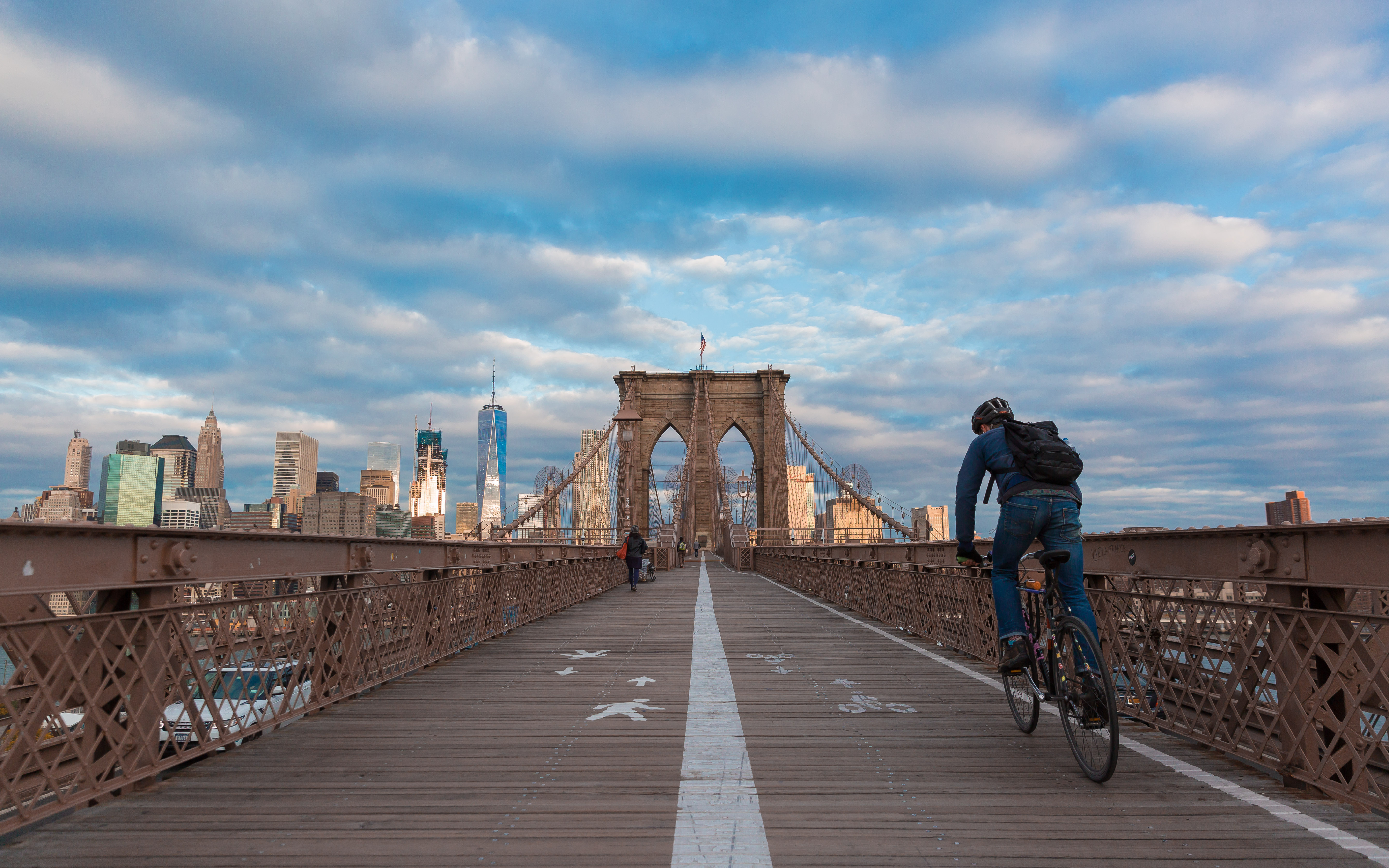 Person with a backpack biking over the Brooklyn Bridge.